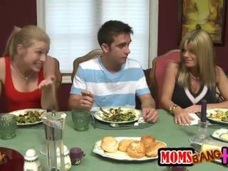Milf stroks une jeune bite sous la table