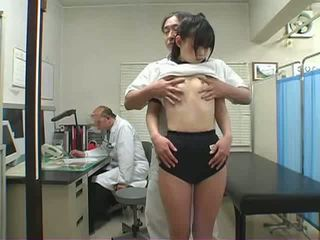 School pediatrician plays with a Asian schoolgirl