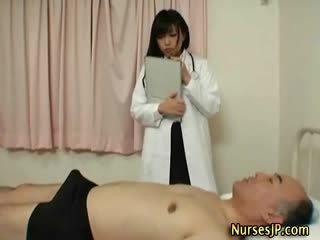 Kåta japanska sjuksköterska gives handen jobb