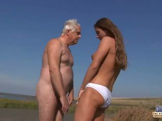 Mladý prsnaté goddess jazdenie starý človek v a divé súložiť na the pláž