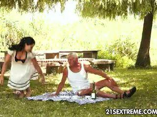 Jovem grávida cutie s bizarro picnic com um avô